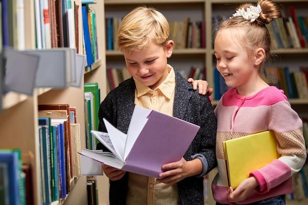 Jungen- und mädchenkinder, die bücher in der bibliothek, im lebensstil der menschen und im bildungskonzept lesen. junge freundschaft und kinderbeziehung im schulkonzept