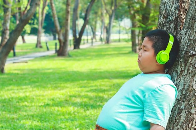 Jungen, welche die grünen musikkopfhörer stehen gegen den baum, geschlossene augen, glücklich tragen