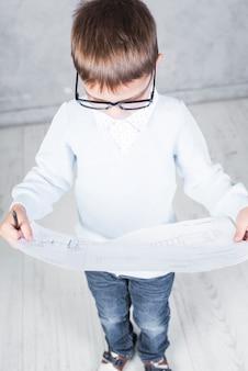 Jungenarchitekt, der papier mit projekt betrachtet