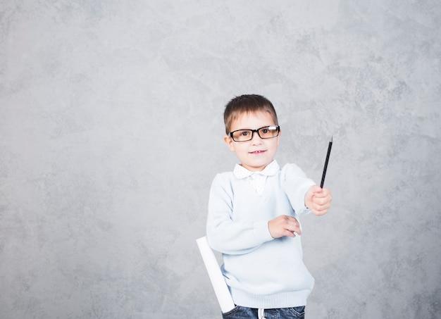 Jungenarchitekt mit papierrolle beim taschenlächeln