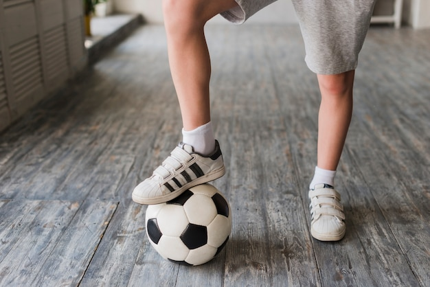 Jungenfuß auf fußball über dem massivholzboden