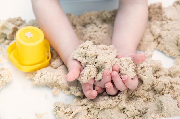 Jungenhände spielen mit kinetischem sand zu hause. frühkindliche bildung. kleinkind spielen.