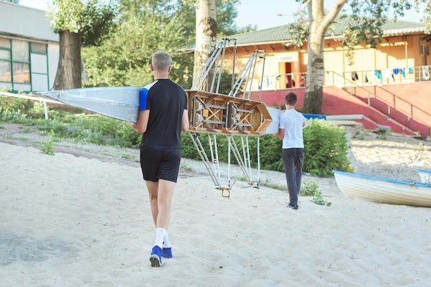 Jungenjugendliche, die mit sportboot kajak zum fluss gehen