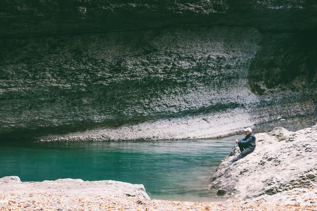 Jungenjugendlicher sitzt auf einem steinstrandblau von einem grünen gebirgsfluss