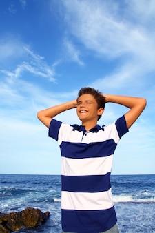 Jungenjugendlichhände im kopf entspannten sich im blauen ozean