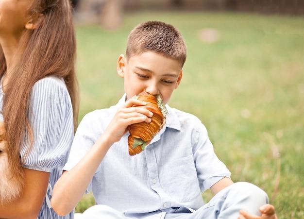 Jungenkind, das auf picknick-sommerferien sitzt und frisch gebackenes croissant-sandwich isst.