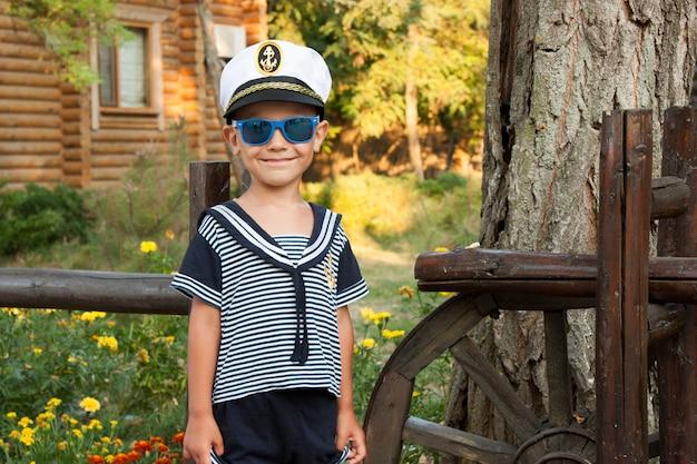 Jungenkind in der kleidung des kapitäns lächelt zart