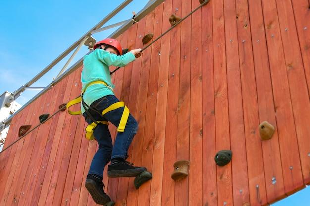 Jungenkind tritt auf die leisten auf der vertikalen wand auf dem hindernislauf im vergnügungspark