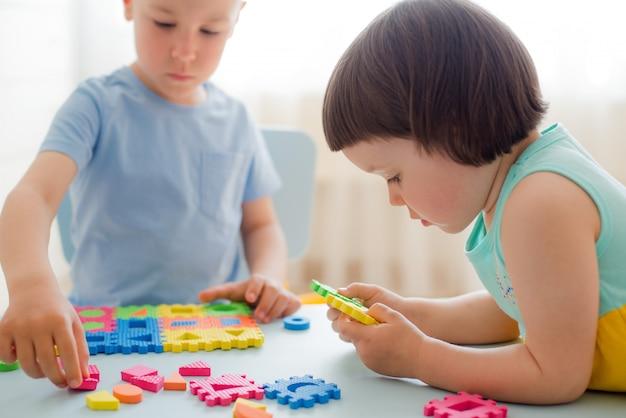 Jungenmädchen sammeln weiches puzzlespiel bei tisch
