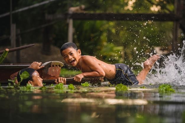 Jungenschwimmen im cannal nahe dem sich hin- und herbewegenden markt damnoen saduak