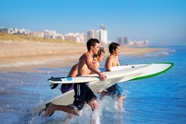 Jungensurfer, die das laufen springend auf surfbretter surfen