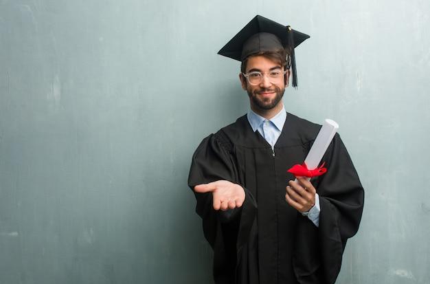 Junger abgestufter mann gegen eine schmutzwand mit einem kopienraum, der etwas mit den händen hält, ein produkt zeigt, lächelnd und fröhlich und bietet eine eingebildete nachricht an