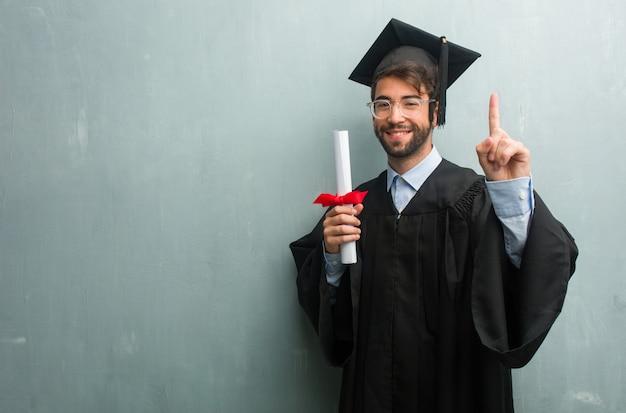 Junger abgestufter mann gegen eine schmutzwand mit einem kopienraum, der nummer eins zeigt