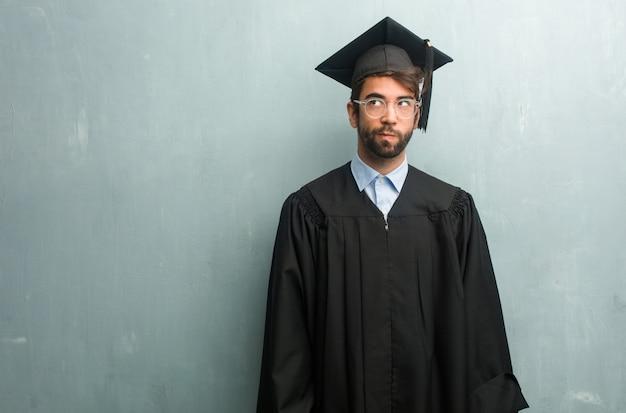 Junger abgestufter mann gegen eine schmutzwand mit einem zweifelnden und verwirrten exemplarplatz