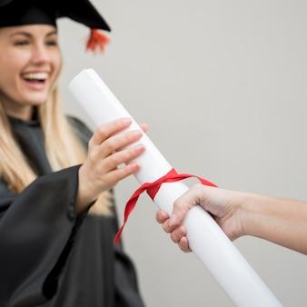 Junger absolvent, der ihr zertifikat erhält