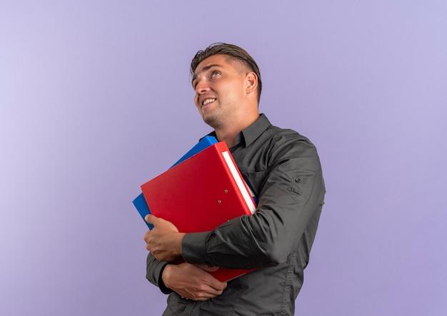 Junger ängstlicher blonder gutaussehender mann hält aktenordner und schaut isoliert auf violettem raum mit kopierraum auf