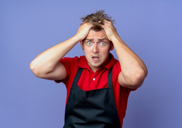 Junger ängstlicher blonder männlicher friseur in der uniform hält kopf isoliert auf violettem raum mit kopienraum