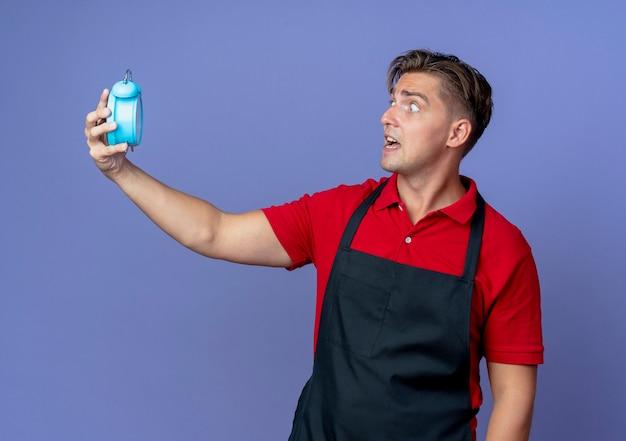 Junger ängstlicher blonder männlicher friseur in uniform hält und betrachtet wecker isoliert auf violettem raum mit kopienraum