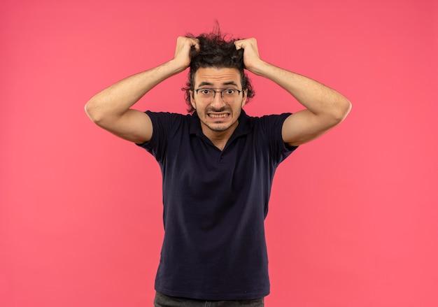 Junger ängstlicher mann im schwarzen hemd mit optischer brille hält haare und sieht auf rosa wand isoliert aus