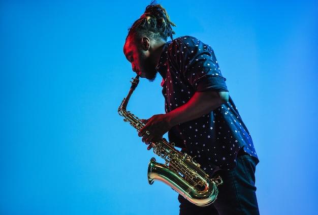 Junger afrikanisch-amerikanischer jazzmusiker, der saxophon spielt