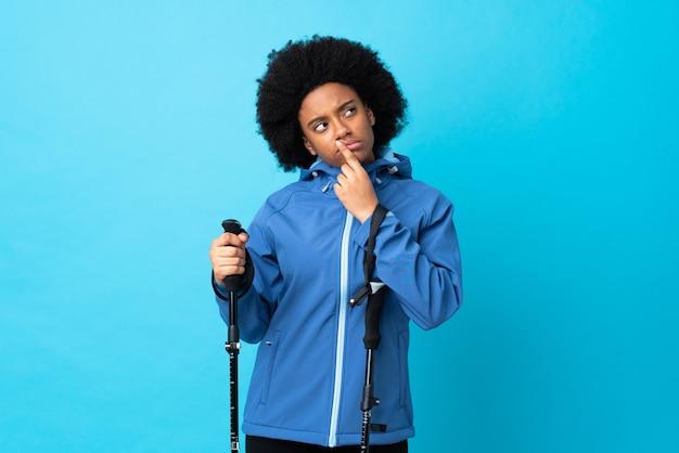 Junger afrikanischer amerikaner mit rucksack und trekkingstöcken lokalisiert auf blau, die zweifel beim aufblicken haben