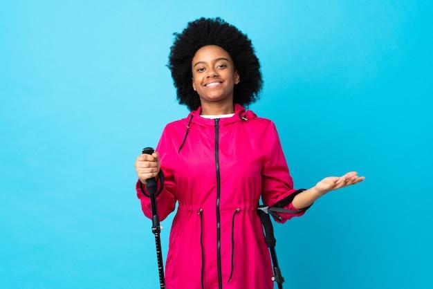 Junger afrikanischer amerikaner mit rucksack und wanderstöcken isoliert auf blau mit zweifeln
