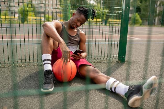 Junger afrikanischer basketballspieler mit dem smartphone, das durch zaun des spielplatzes und scrollen im smartphone entspannt