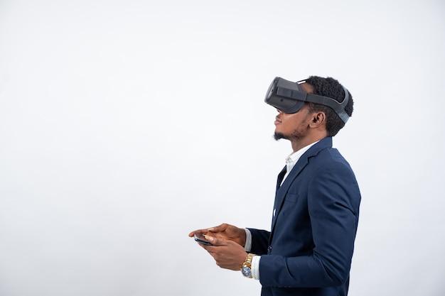 Junger afrikanischer geschäftsmann, der ein virtual-reality-headset trägt und sein telefon benutzt