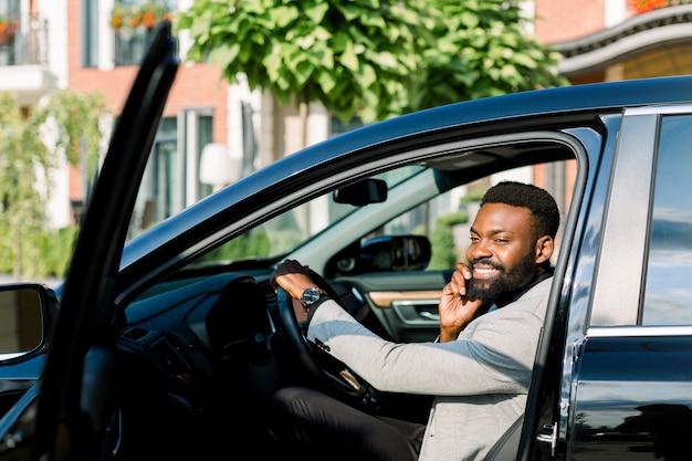 Junger afrikanischer geschäftsmann, der in seinem schwarzen auto sitzt und einen anruf macht und lächelt. bürogebäude
