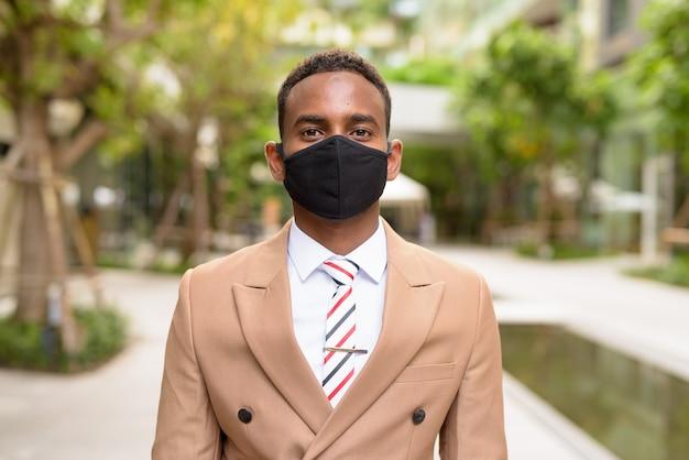 Junger afrikanischer geschäftsmann, der maske zum schutz vor coronavirus-ausbruch in der stadt mit natur trägt