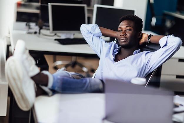 Junger afrikanischer geschäftsmann, der sich in seinem büro entspannt. zeit für die erholung nach der arbeit.