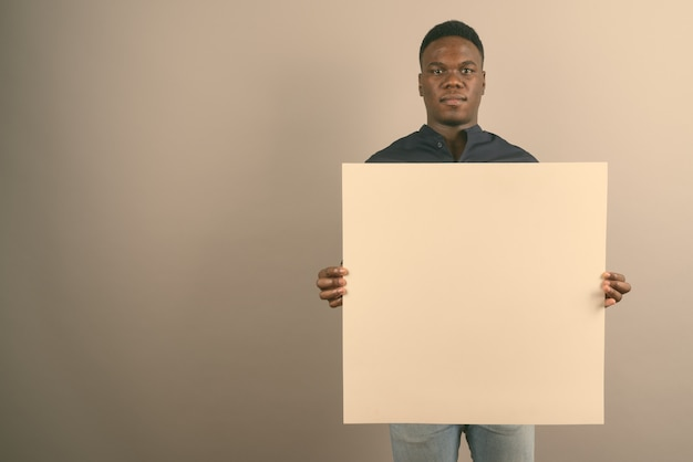Junger afrikanischer geschäftsmann, der weiße tafel hält