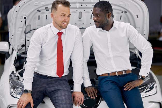 Junger afrikanischer geschäftsmann stellt fragen über auto, das im autohaus vorgestellt wird
