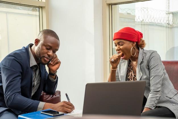 Junger afrikanischer geschäftsmann und frau, die sich in einem meeting gelangweilt fühlen