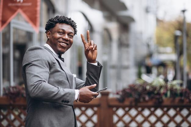 Junger afrikanischer geschäftsmann unter verwendung des telefons