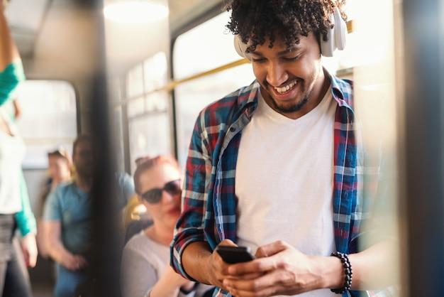 Junger afrikanischer kerl, der die musik hört und smartphone während des fahrens in öffentlichen verkehrsmitteln benutzt.