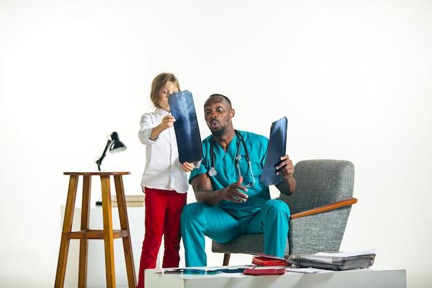 Junger afrikanischer männlicher kinderarzt, der dem kind röntgen erklärt