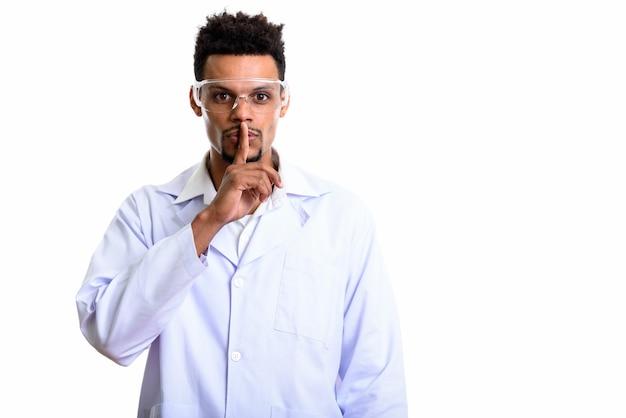 Junger afrikanischer mann arzt mit finger auf lippen lokalisiert auf weiß