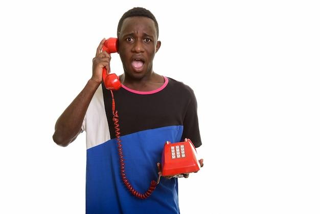 Junger afrikanischer mann, der am alten telefon spricht und schockiert aussieht