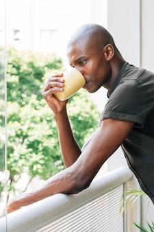 Junger afrikanischer mann, der auf dem geländer den kaffee trinkend sich lehnt