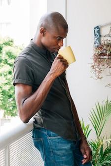 Junger afrikanischer mann, der auf dem geländer des balkons den kaffee trinkend sich lehnt
