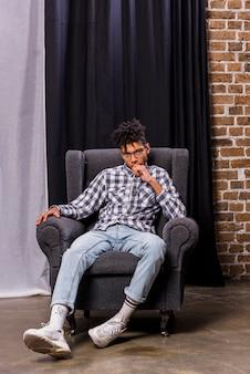 Junger afrikanischer mann, der auf stuhl vor dem vorhang betrachtet kamera sitzt
