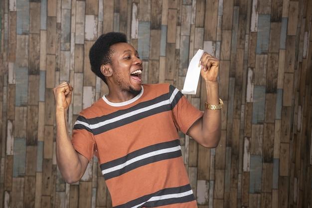 Junger afrikanischer mann, der aufgeregt und glücklich fühlt, während er einen zettel hält