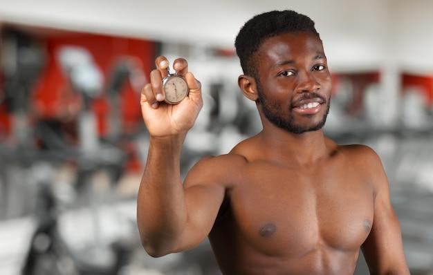 Junger afrikanischer mann, der die silberne retro- stoppuhr zählt zeit hält