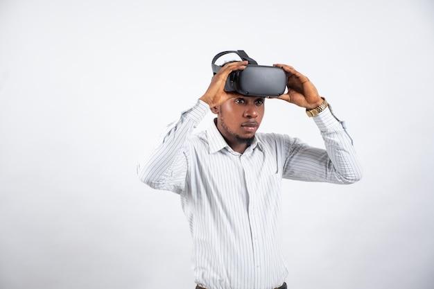 Junger afrikanischer mann, der ein virtual-reality-headset aufsetzt