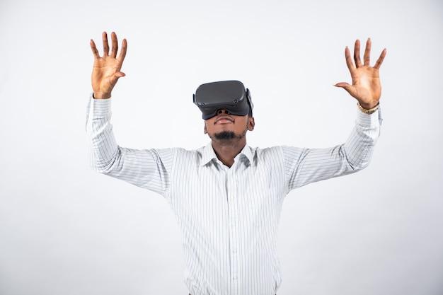 Junger afrikanischer mann, der ein virtual-reality-headset verwendet und mit seinen händen gestikuliert
