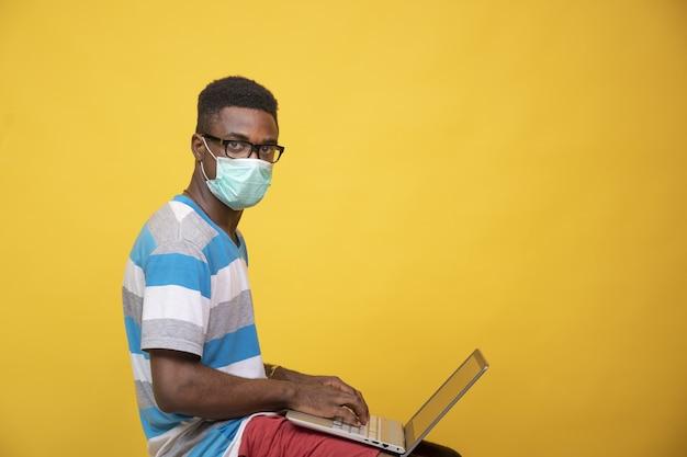 Junger afrikanischer mann, der eine brille und eine gesichtsmaske trägt, während er an seinem laptop arbeitet