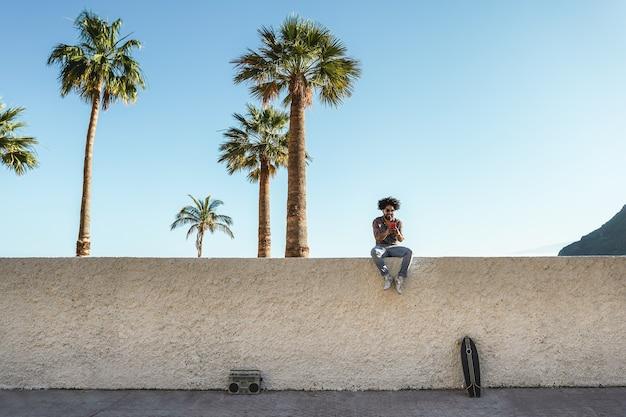 Junger afrikanischer mann, der handys mit palmen benutzt