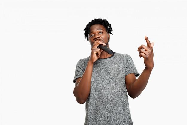 Junger afrikanischer mann, der im mikrofon auf weiß singt.