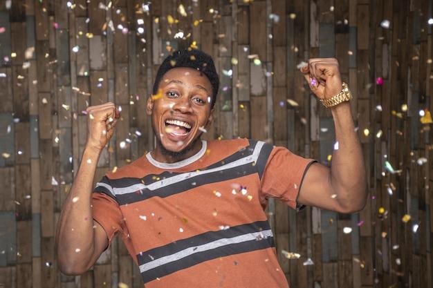 Junger afrikanischer mann, der mit herumschwebenden konfetti feiert